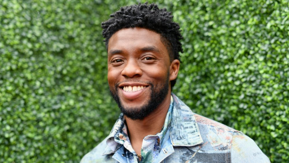 Chadwick Boseman in a multi-colored jean jacket and button-up, smiling outside
