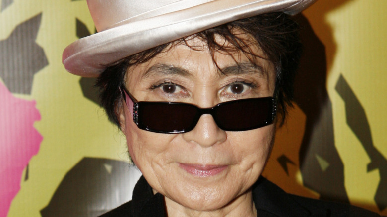 Yoko Ono poses in sunglasses and a hat