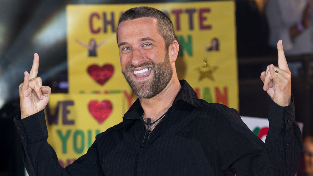Dustin Diamond posing for a photo with hands raised