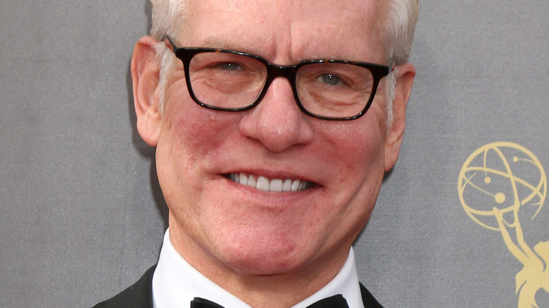 Tim Gunn smiling and wearing glasses at the Emmy Awards