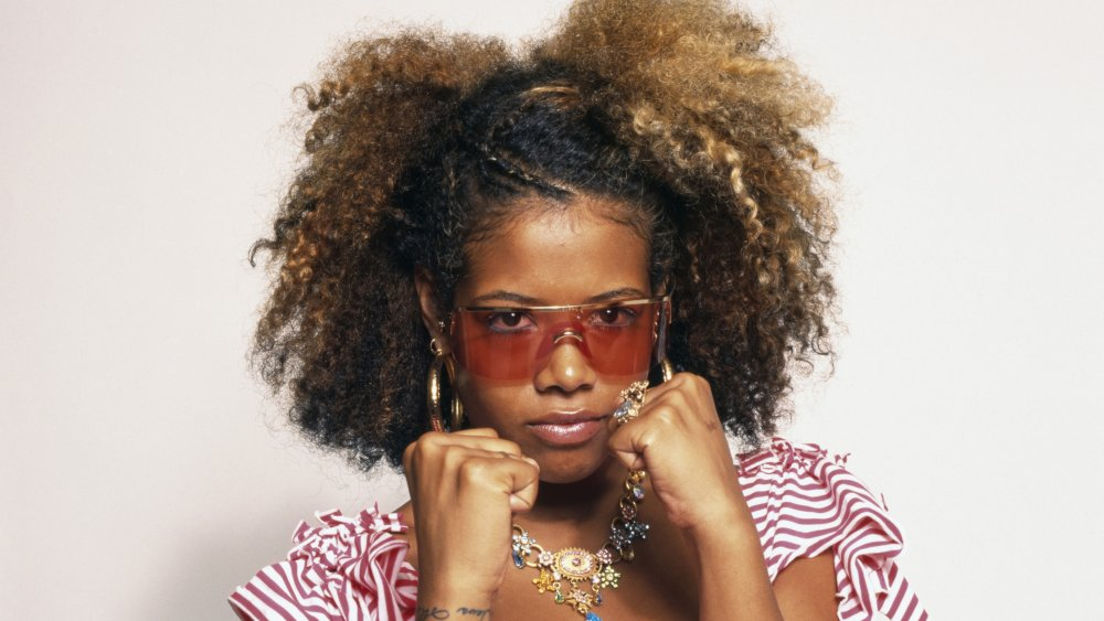Kelis with fists up and red sunglasses