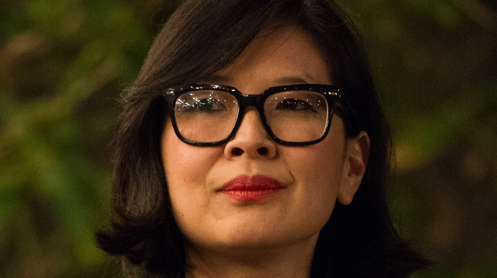 SuChin Pak listening and wearing thick, black-rimmed glasses