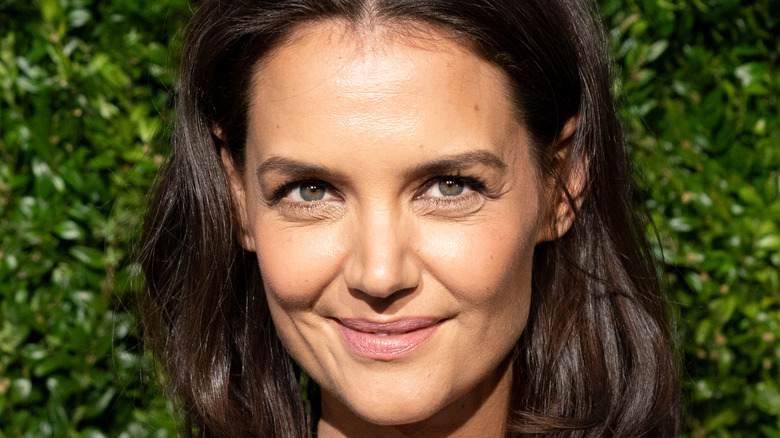 Katie Holmes in front of greenery