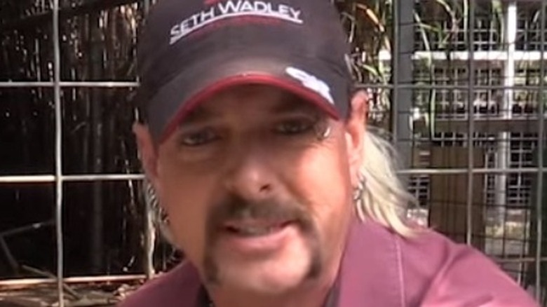 Joe Exotic smiling in front of cages