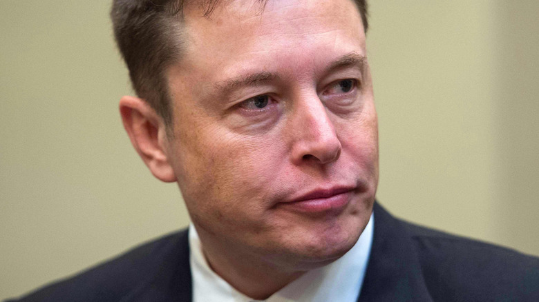 Elon Musk at a conference looking to the side with a serious expression