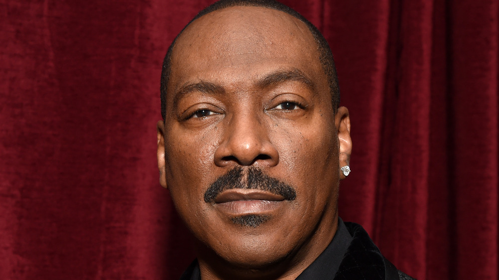 Eddie Murphy poses in front of a red curtain in 2019