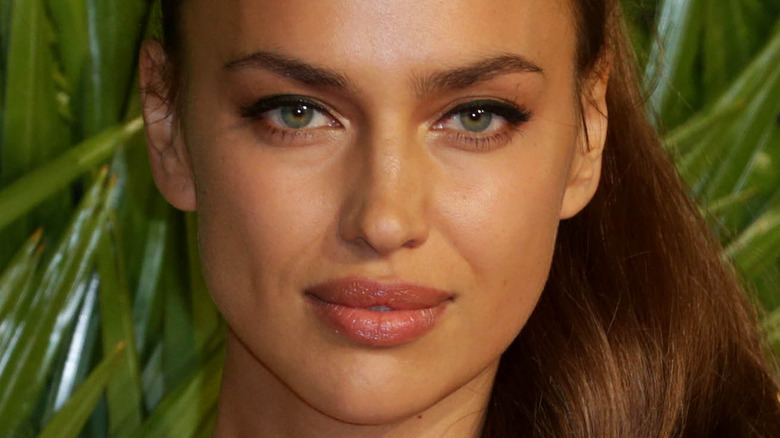 Irina Shayk poses in front of green background.