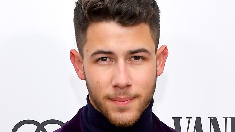 Nick Jonas looks straight ahead smiling slightly posing for cameras