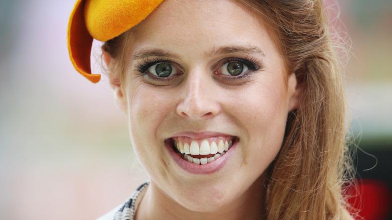 Princess Beatrice smiling in an orange hat