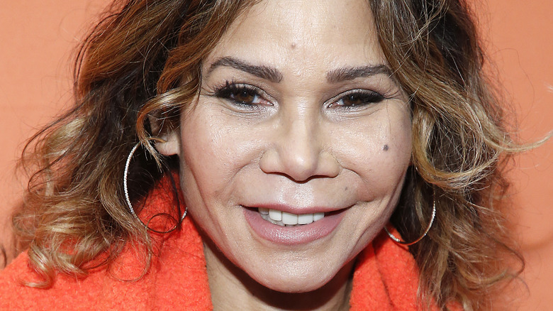 Daphne Rubin-Vega, smiling, curly hair down, against an orange background, 2020 photo