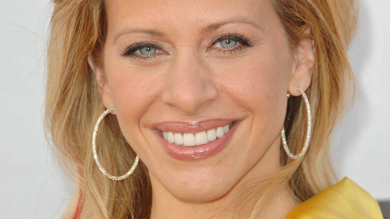 Dina Cantin smiling and wearing hoop earrings