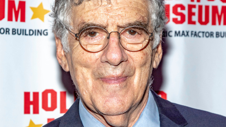Elliott Gould smirking on red carpet at an event