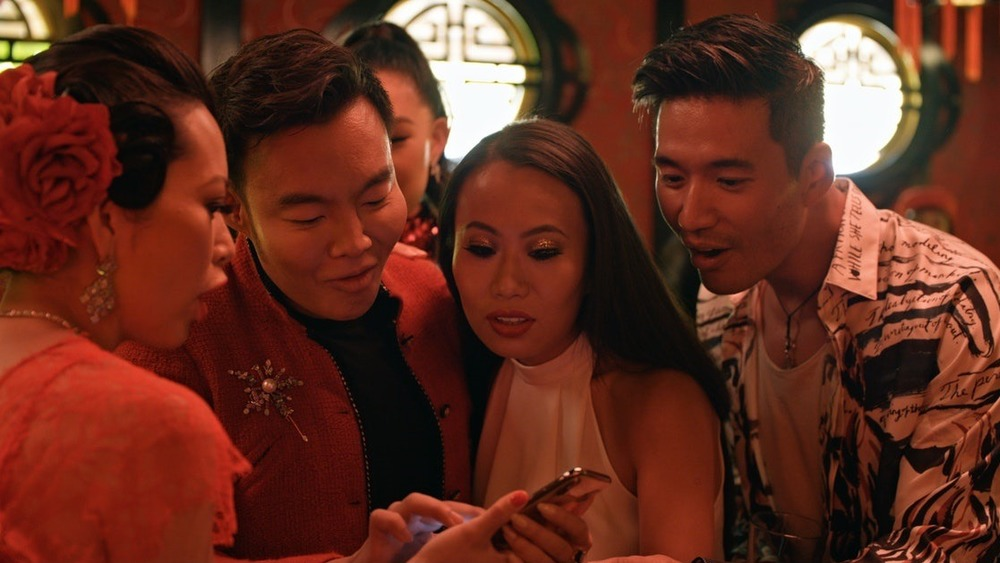 The cast of Netflix's Bling Empire looking at a phone on set
