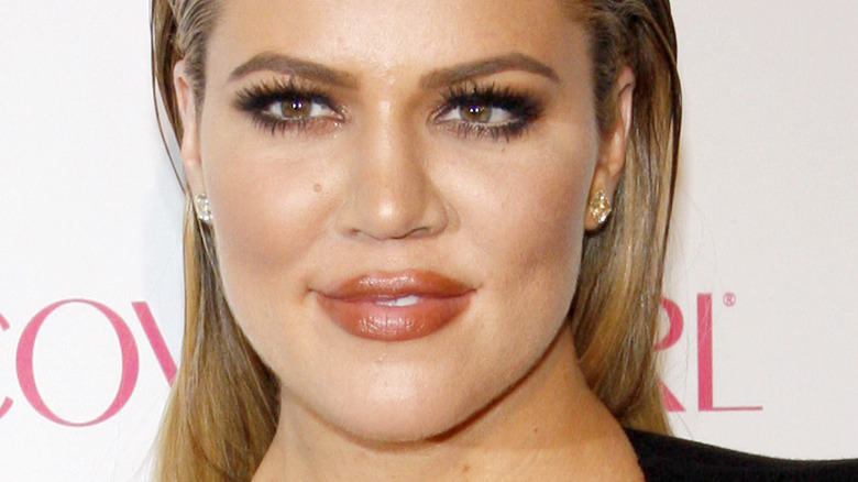 Khloé Kardashian smiling and looking to side