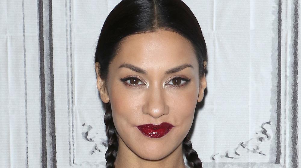 Janina Gavankar wearing dark red lipstick and braids smiling