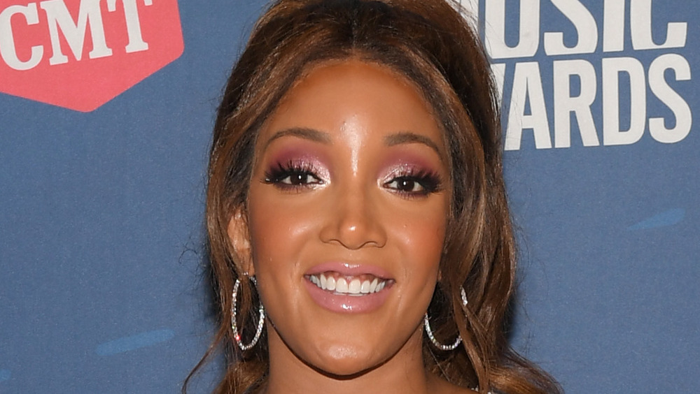 Mickey Guyton wears dangly hoop earrings while smiling for the cameras on the CMT red carpet