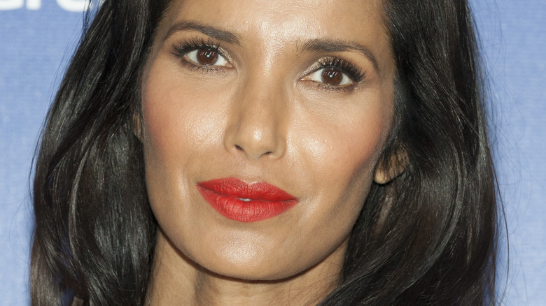 Padma Lakshmi posing with slight smile and red lipstick