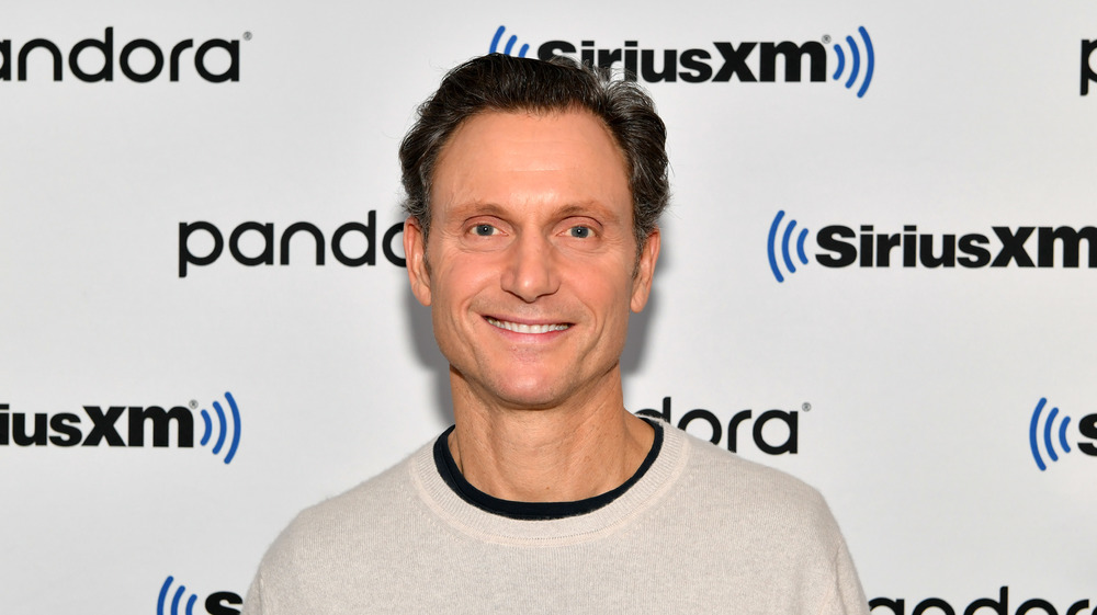 Tony Goldwyn smiles in front of a camera wearing a cream sweater