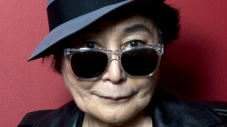 Yoko Ono poses in leather jacket, glasses and a hat.