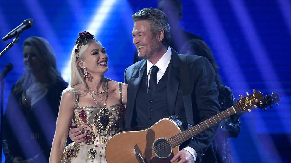 Gwen Stefani and Blake Shelton smiling on stage