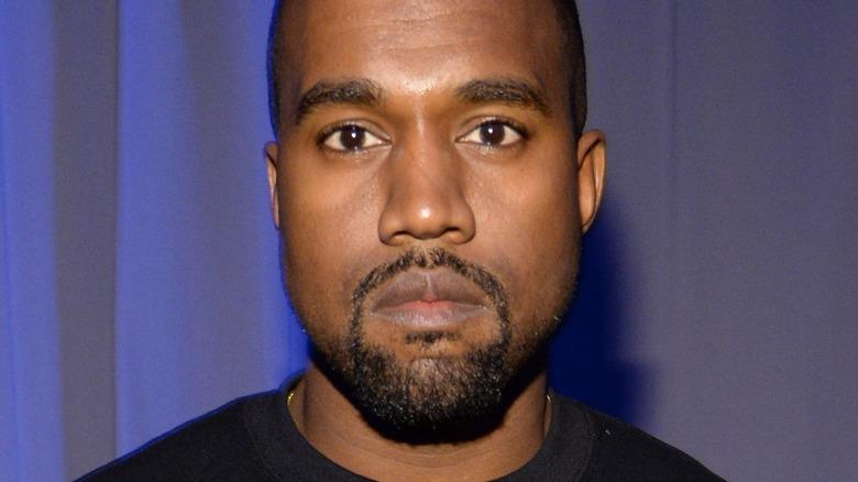 Kanye West poses in a black sweatshirt.