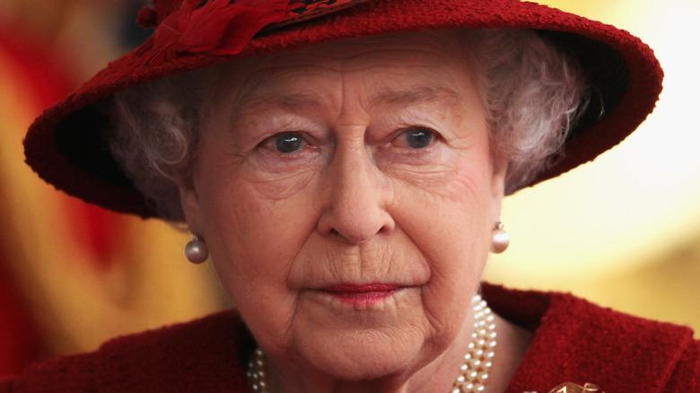 Queen Elizabeth wearing a red hat