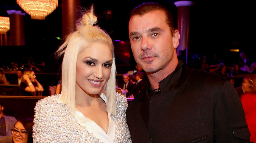 A smiling Gwen Stefani and a serious-looking Gavin Rossdale posing at an event a year before their divorce