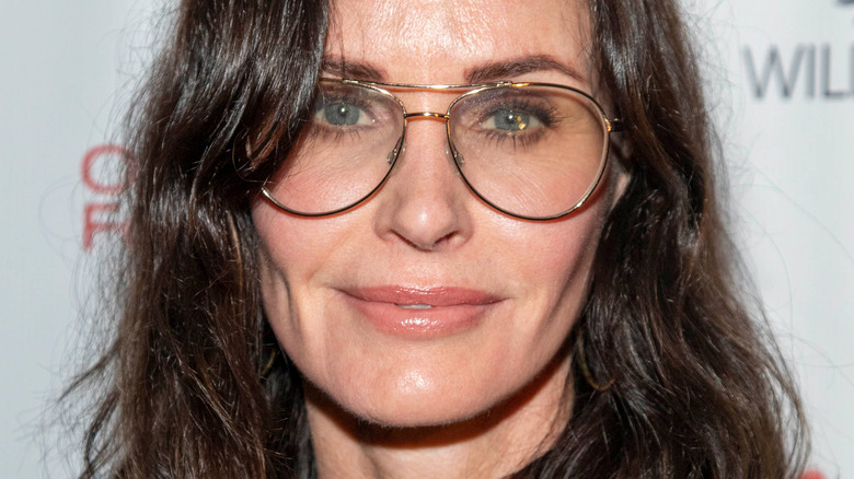 Courteney Cox on red carpet wearing glasses