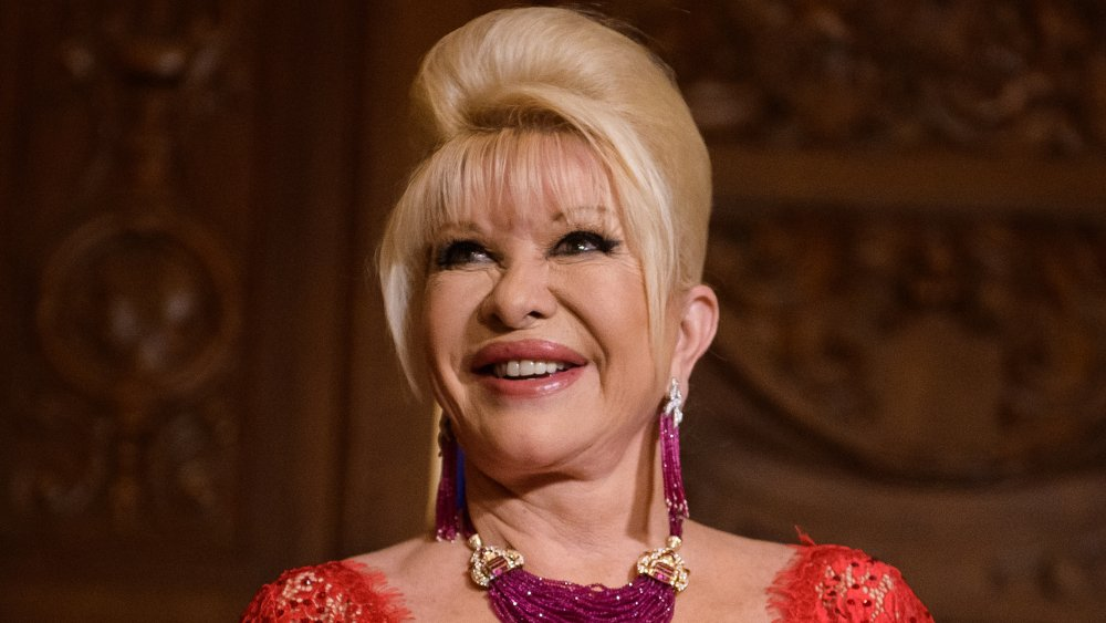 Ivana Trump in a red dress, smiling while looking up and to the side