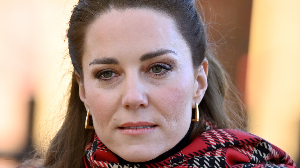 Kate Middleton wearing something plaid over her neck