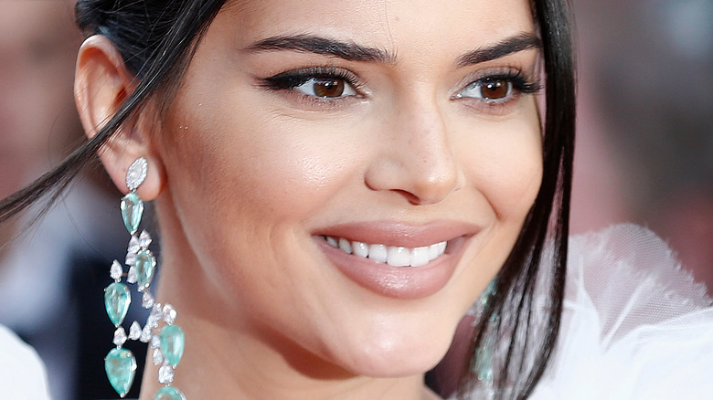 Kendall Jenner on the red carpet smiing to the side with long earrings