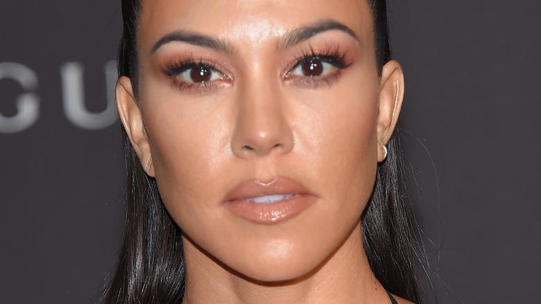 Kourtney Kardashian with serious expression on the red carpet