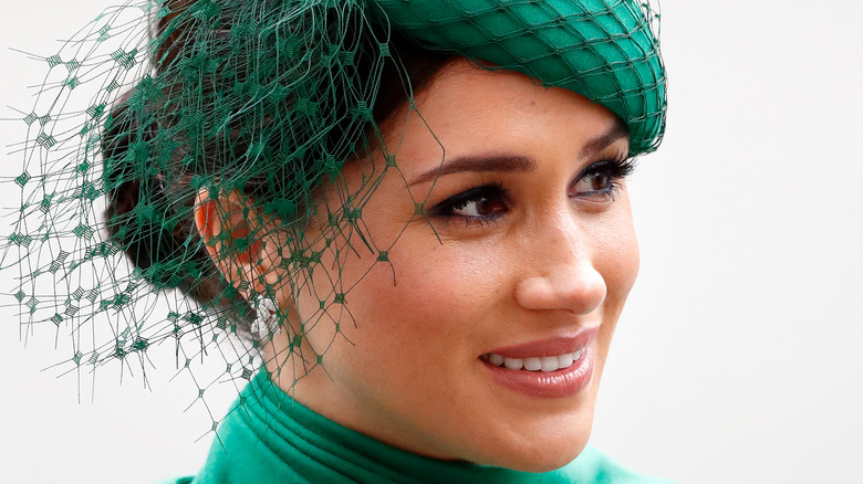 Meghan Markle smiling and looking to the side in green fascinator