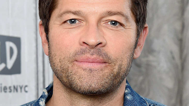 MIsha Collins with denim jacket and serious expression