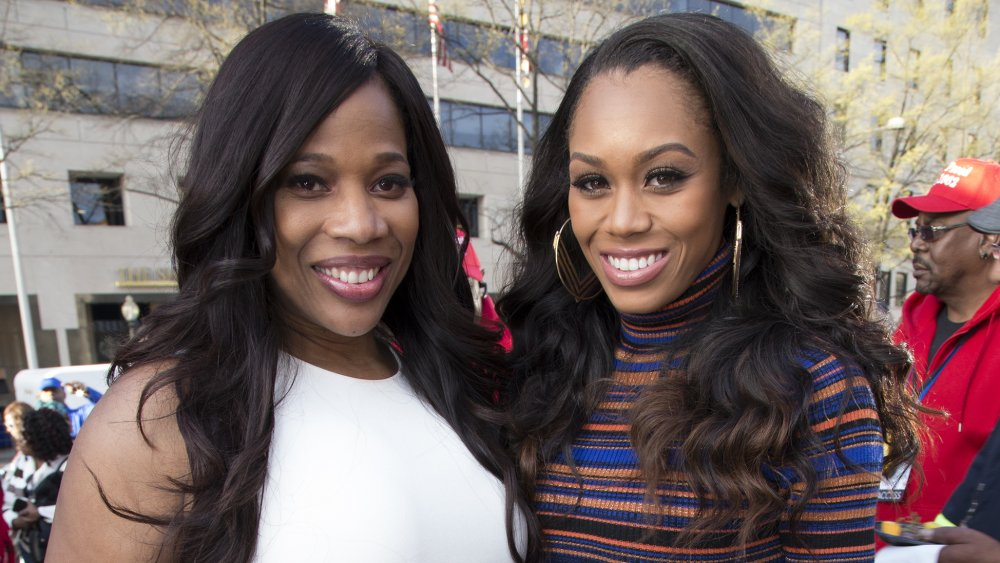 Charrisse Jordan and Monique Samuels smiling while posing arm in arm