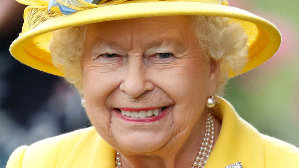 Queen Elizabeth II smiling in a yellow outfit and matching hat