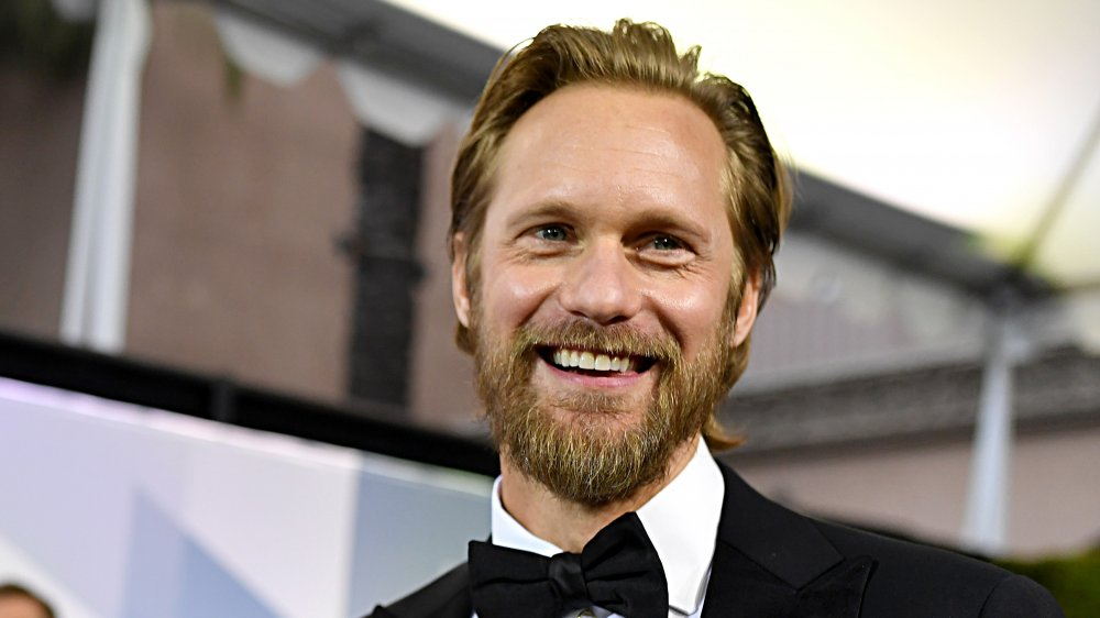 Alexander Skarsgård smiling in a suit